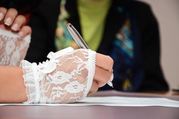 Женщина подписывает документ