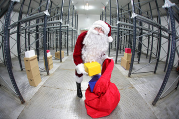 Santa Claus preparing for Christmas in storehouse