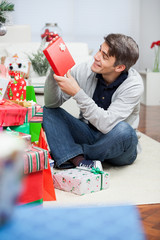 Man Looking At Christmas Present In House