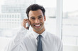 Close-up of a smiling elegant businessman using cellphone
