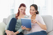 Happy relaxed female friends using digital tablet at home