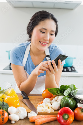 Woman text messaging in front of vegetables in kitchen