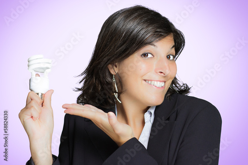 Young woman shows an energy saving light bulb smiling