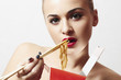 beautiful woman are eating noodles.red lips.Chinese sticks.