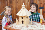 Happy kids building a bird house
