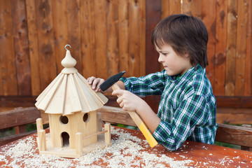 Boy building a bird house - mounting the last roof piece