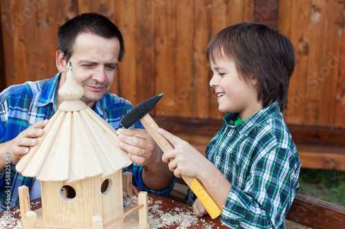 Father and son building a bird house or feeder