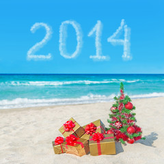 Christmas tree and gift boxes on sea beach. Concept for New Year