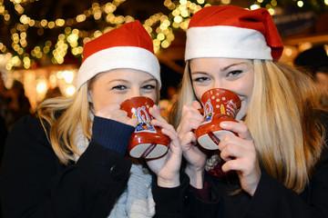 Freundinnen trinken Glühwein auf Christkindlmarkt