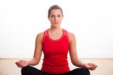 Woman sitting cross legged doing a yoga pose in the studio