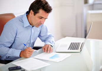 Adult hispanic businessman looking at his notes