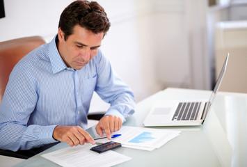 Hispanic employee working with his calculator