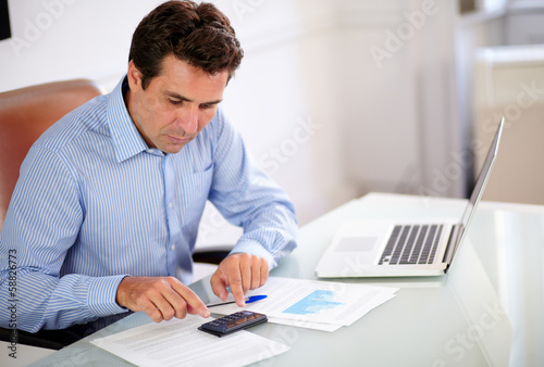 Hispanic employee working with his calculator