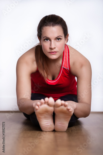 Female in her twenties sitting on a studio floor exercising