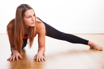 Young woman exercising - stretching leg out to the side