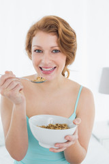 Smiling young female with a bowl of cereal sitting on bed