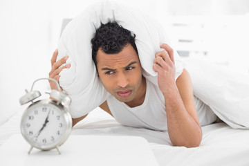 Man covering ears with pillow as he looks at alarm clock in bed