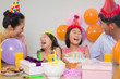 Cheerful family with cake and gifts at a birthday party