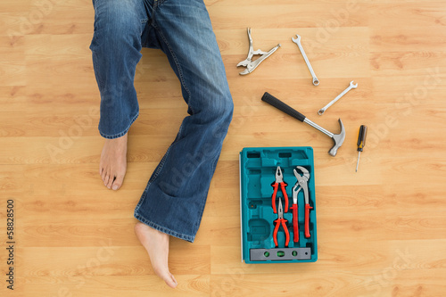 Man lying with several tools on parquet floor