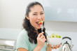 Side view portrait of a woman eating salad in kitchen