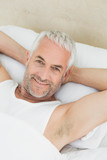 Portrait of a smiling mature man resting in bed