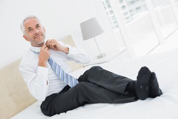 Mature businessman adjusting neck tie in bed