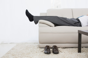 Low section of a businessman resting on sofa in living room
