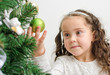 Little girl decorates the Christmas tree