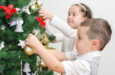 Children decorating Christmas tree with balls.