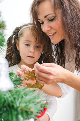 Woman and her daughter decorating the Christmas tree