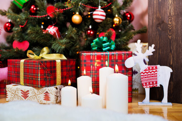 candle on the background of the Christmas tree with gifts