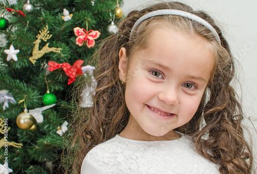 Happy little girl over christmas tree