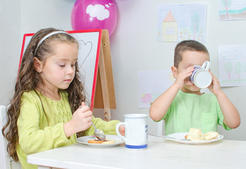 Little girl and boy is eating in kindergarten.