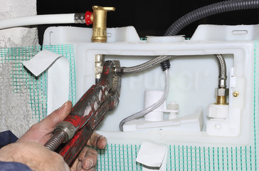 Worker assembles a manifold water system with focus on hands