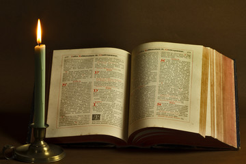 Opened old book and candle