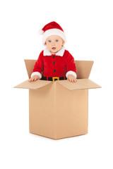Cute baby-santa with beautiful blue eyes inside the box