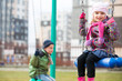 Children swing against urban landscape