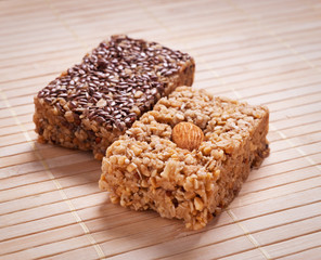 Homemade flapjack with almonds and seed on wooden mat.