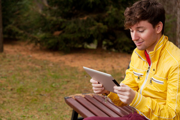 Man with tablet sits in the Park