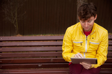 Man with tablet sits on bench in the Park