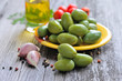 Green olives with garlic and pepper on a wooden background