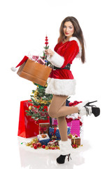 Sensual woman in Santa costume in front of a Christmas tree