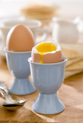 sunny breakfast table with two soft-boiled eggs.