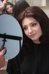 Brunette woman with new hairstyle looking mirror