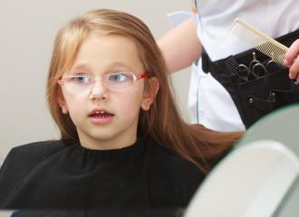 Hairdresser combing hair little girl child in hairdressing salon