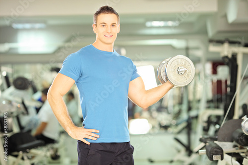 Smiling muscular man lifting weight in fitness club