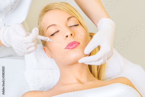Young woman receiving botox injection in cheeks