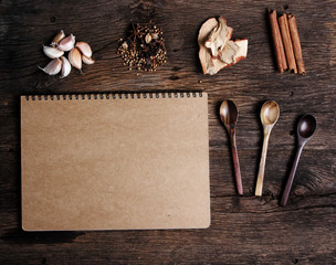 Still life with spices and notebook paper on old wooden table