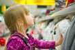 Adorable girl select winter clothes in supermarket