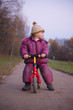 Adorable girl ride on learner bike in autumn park